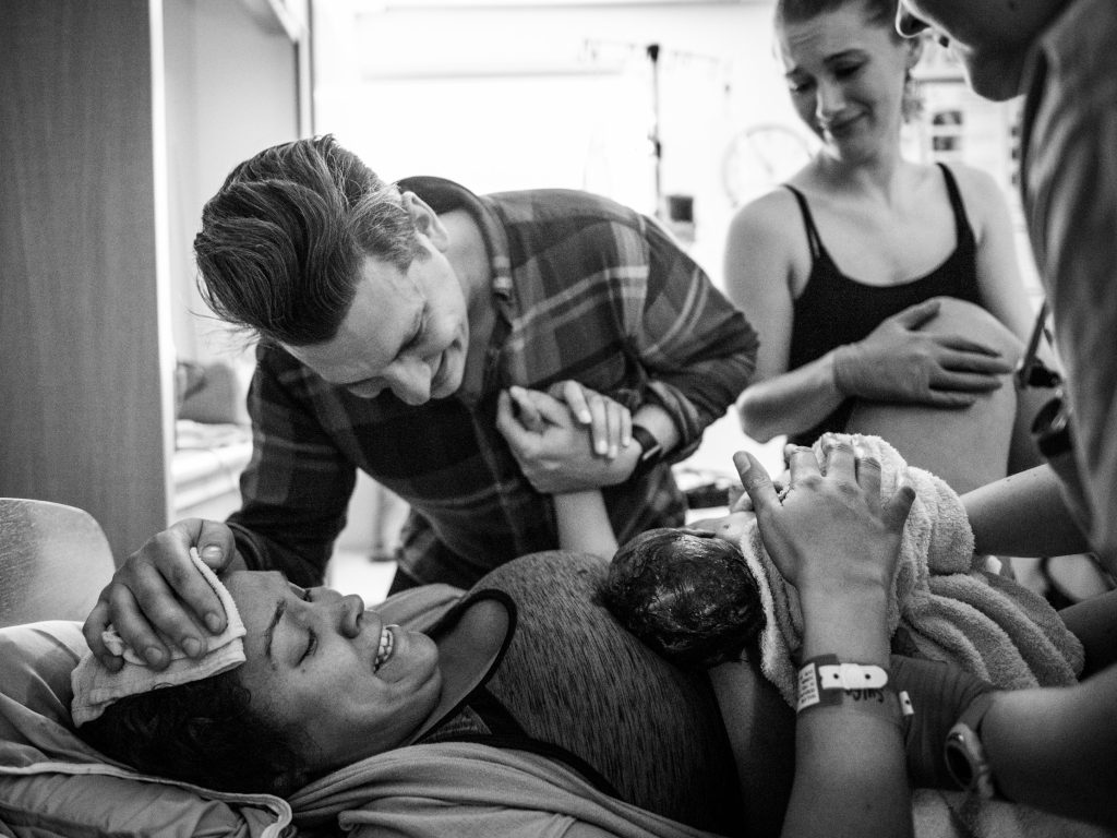 A photo of a mother and her partner looking at their newborn child.