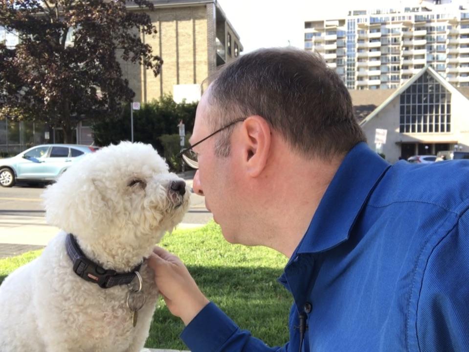 Jordan Green pets his dog, Joey, a fluffy little white dog.