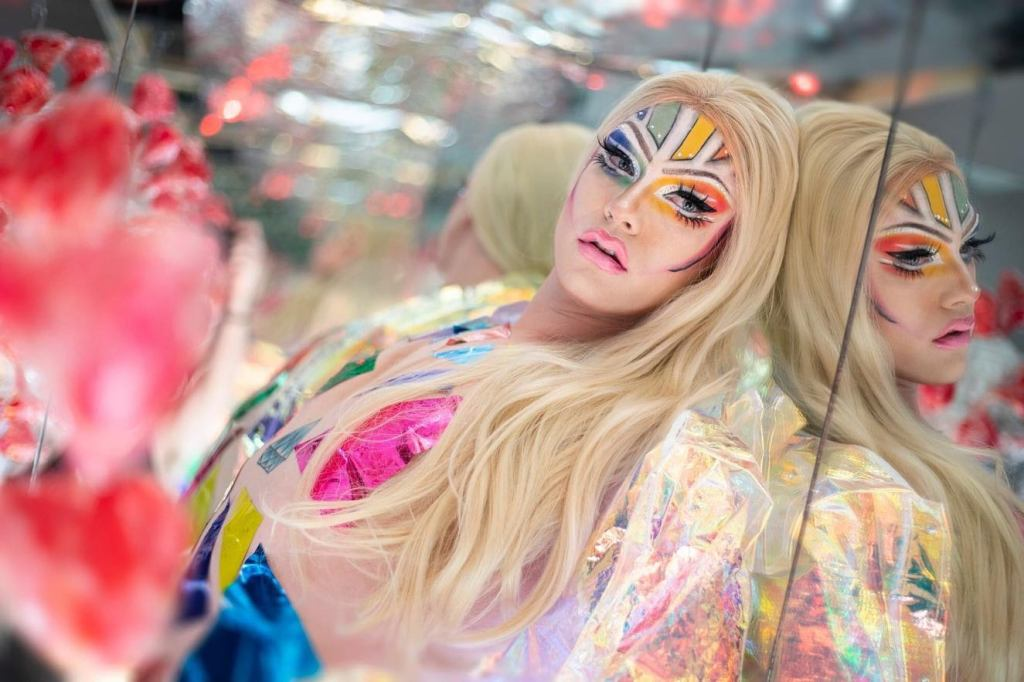 A photo of Max Sovereign, portraying his drag persona Sophia Sapphire. Sophia is dressed in a rainbow outfit with rainbow-coloured face paint on. She is wearing a blonde wig and leaning against a mirror.
